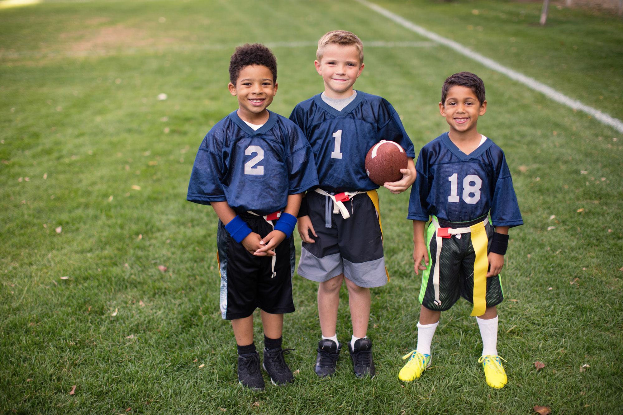 Three boys on a flag football team pose together.